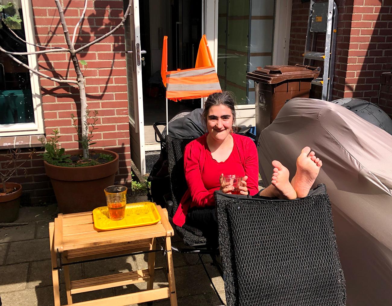 Een foto van Anemoon in de zon op haar ligfietstandem. Ze zit op de achterste stoel, heeft een kopje thee vast en heeft haar blote voeten op de rug van de voorste stoel gelegd.