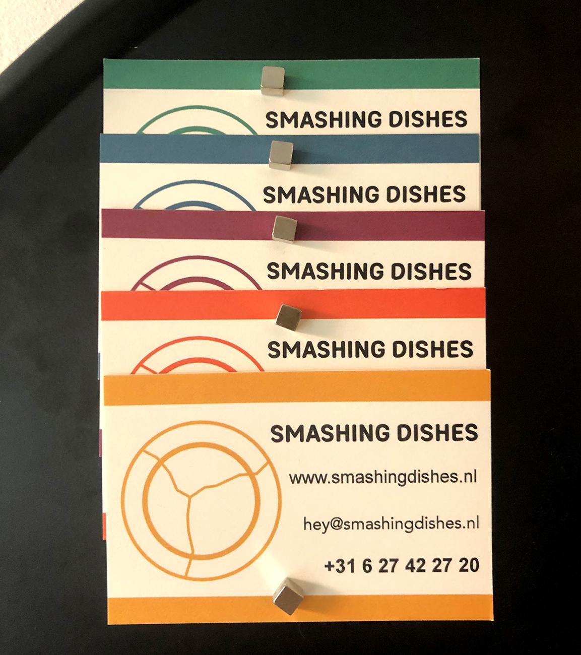 Foto van vijf visitekaartjes van Samshing Dishes die een regenboog vormen van de verschillende kleuren op de website: groen, blauw, paars, oranje en geel, van boven naar beneden.